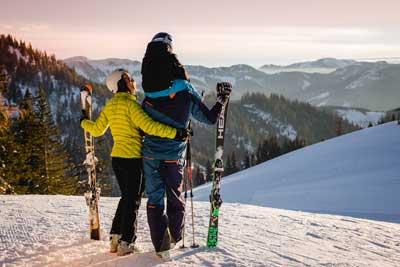 Familie steht am Pistenrand ganz oben beim Niederalpl und schaut sich das herrliche Winterpanorama an.